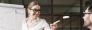 Business-Frau zeigt auf Flipchart